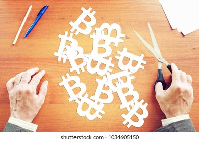 Concept of investment to crypto-currencies. Man cuts out from paper many bitcoin signs