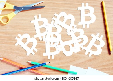 Concept of investment to crypto-currencies. Many bitcoin signs are cut out from paper on the wooden desk