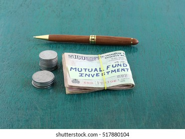 Concept of investment in a mutual fund indicated by a handwritten note placed on folded Indian currency rupee notes.