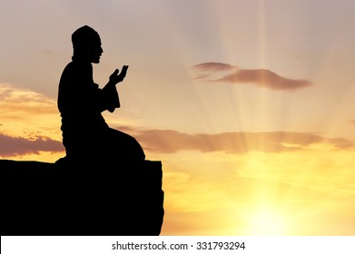 Concept of Islam is the religion. Silhouette of man praying on a hilltop at sunset