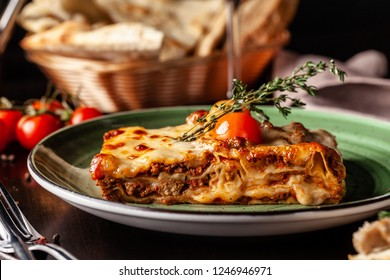 The concept of Italian cuisine. Baked lasagna with minced bolognese, pasta, cherry tomatoes lies on a green plate in a restaurant. A glass of red wine and bread basket on the table