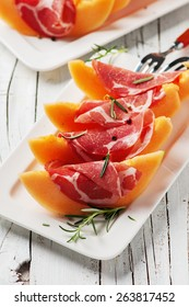 Concept of italian food with melon and prosciutto, selective focus