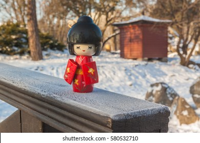 Concept of  Japanese custom of admiring the snow (Yukimi). Kokeshi Japanese doll (mass produced products) on the background of the tea house and lantern.