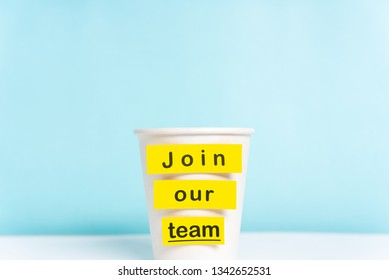Concept of join our team or onboarding process. Paper cup with yellow top on desk with a paper cup over blue background.