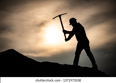 Concept Labor Day: Labor man standing holding a pickaxe with a warm sunset light