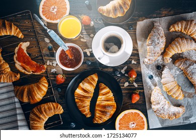 The concept of a large and varied breakfast. different croissants and jams, coffee and amelsin juice, grapefruit and strawberries on the table top view