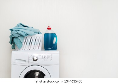 Concept of laundry process. White washing machine standing isolated inside bright light flat interior. Gel detergent soap with basket of lien on top of laundromat
