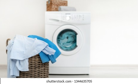 Concept of laundry process. Wooden basket with clothes standing against washing machine inside apartment with light interior