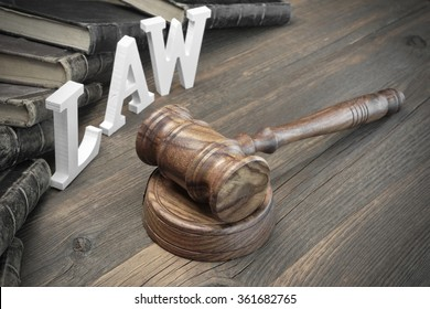 Concept For Law, Lawsuit, Court, Crime. Judges Gavel, Sign Law Old Law Book On The Rough Wooden Vintage Textured Table Background.
