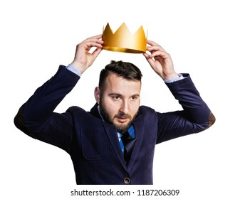 The concept of leadership, excellence. A portrait of a bearded man, he dresses a golden crown on his head. Isolated on white background.