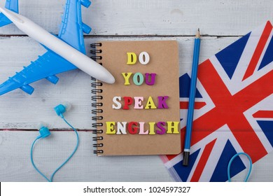 "Concept of learning English language - colorful letters with text ""Do you speak English"", flag of the UK, airplane, headphones on white wooden background"