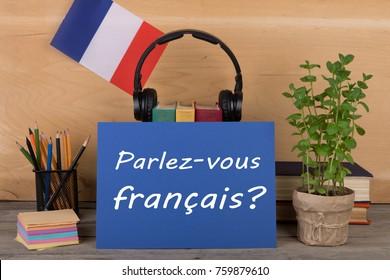"concept of learning French language - paper with text ""Parlez-vous français?"" (Parlez vous francais?), flag of the France, books, headphones, pencils on wooden background"