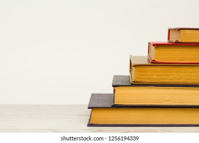 The concept of learning and knowledge. Books on a wooden surface and a white background.