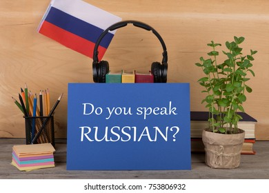 "Concept of learning the russian language - paper with text ""Do you speak Russian?"", flag of the Russian Federation, books, headphones, pencils on wooden background"