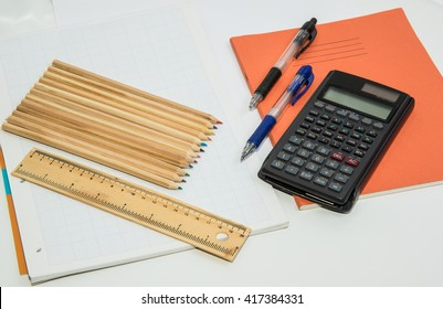 The concept of learning shown with a calculator & pencils on a background of graph paper / Pens and Pencils