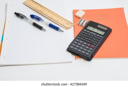 The concept of learning shown with a calculator & pens on a background of graph paper / Tools for writing
