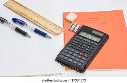 The concept of learning shown with a calculator & pens on a background of graph paper / writing tools