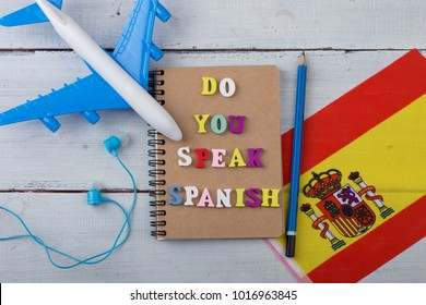 "Concept of learning the spanish language - colorful wooden letters with text ""Do you speak spanish"", flag of the Spain, model airplane, headphones, pencil on white wooden background"