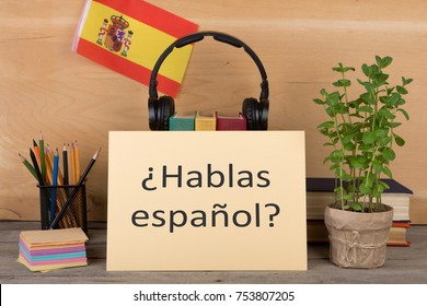 "Concept of learning the spanish language - paper with text ""¿hablas español?"" (hablas espanol), flag of the Spain, books, headphones, pencils on wooden background"