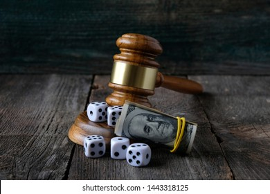 Concept of legal regulation of gambling, justice gavel, money and dice on the background of an old wooden table.