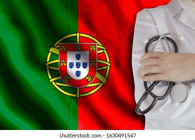 The concept of the level of medicine in the country, the salary of a doctor, the incidence rate in the country. Doctor holds a stethoscope on the background of the flag of Portugal