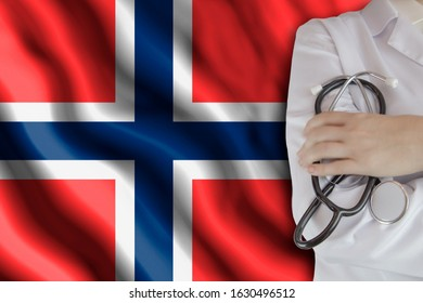 The concept of the level of medicine in the country, the salary of a doctor, the incidence rate in the country. Doctor holds a stethoscope on the background of the flag of Norway