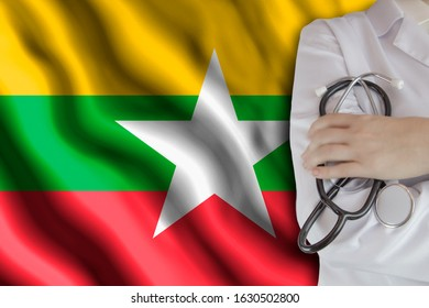 The concept of the level of medicine in the country, the salary of a doctor, the incidence rate in the country. Doctor holds a stethoscope on the background of the flag of Myanmar