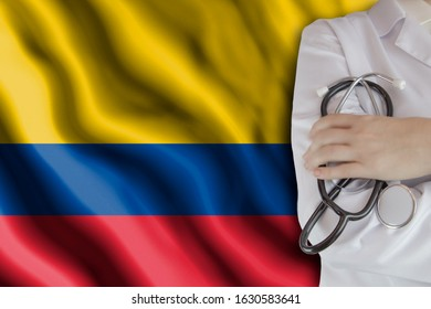 The concept of the level of medicine in the country, the salary of a doctor, the incidence rate in the country. Doctor holds a stethoscope on the background of the flag of Colombia