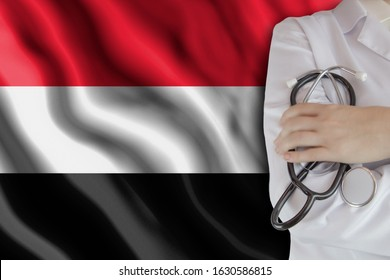 The concept of the level of medicine in the country, the salary of a doctor, the incidence rate in the country. Doctor holds a stethoscope on the background of the flag of Yemen
