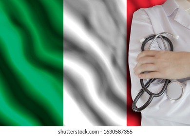 The concept of the level of medicine in the country, the salary of a doctor, the incidence rate in the country. Doctor holds a stethoscope on the background of the flag of Italy