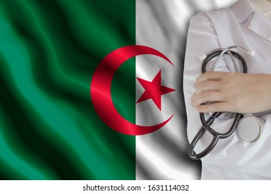 The concept of the level of medicine in the country, the salary of a doctor, the incidence rate in the country. Doctor holds a stethoscope on the background of the flag of Algeria