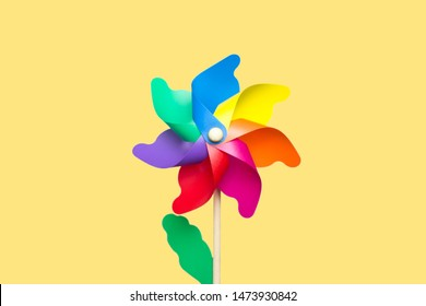 Concept of LGBT, lesbian and gay people, nostalgic childhood, rainbow flag. Rainbow pinwheel at the center of the image with a yellow background. Isolated