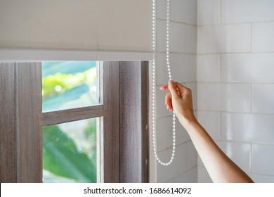 Konzept der Regelung des Lichtbereichs. Die gepfropfte Ansicht der Frau ziehen Seil und geschlossene moderne weiße jalousie auf Fenstern im Zimmer in ihrem gemütlichen Haus