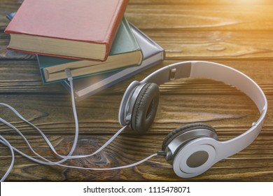 The concept is to listen to audiobooks. white headphones are connected to the book.