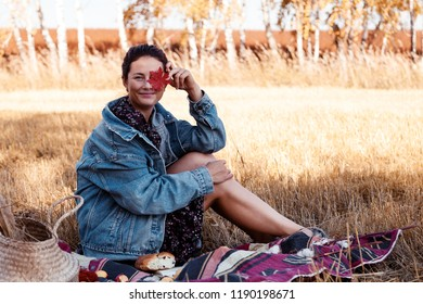 The concept of livestyle and family outdoor recreation in autumn. Picnic in the fresh air: a young woman in a denim jacket and dress enjoying nature. plaid with a picnic basket, apples, wine.