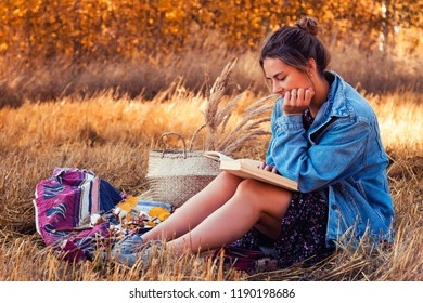 The concept of livestyle and family outdoor recreation in autumn. Picnic in the fresh air: a young woman in a denim jacket and dress read books on plaid with a picnic basket, apples, wine.