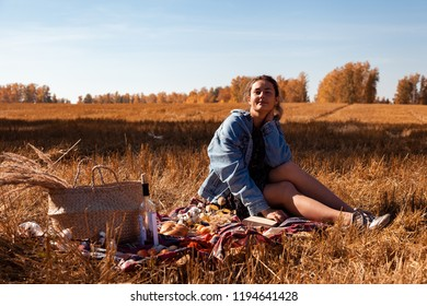 The concept of livestyle and family outdoor recreation in autumn. A young woman in a denim jacket and dress enjoying nature on plaid with a picnic basket, apples, wine. On the  background autumn field