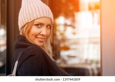 The concept of livestyle  outdoor in autumn. Close up of a young woman student in a warm autumn clothes looking thoughtfully, posing for the camera on the background of shop windows