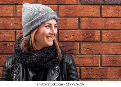 The concept of livestyle  outdoor in autumn. Close up of a young woman student in a warm autumn clothes looking funny, smilling, posing for the camera on the background of shop windows