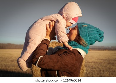 The concept of livestyle  outdoor in autumn. Close up of a young woman student in a warm autumn clothes with baby looking funny, smilling, posing and playing with daughter  on the  field stack