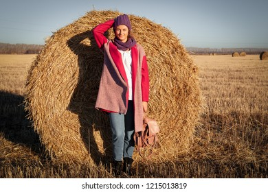 The concept of livestyle  outdoor in autumn. Close up of a young woman student in a warm autumn clothes looking funny, smilling, posing for the camera  around haystick