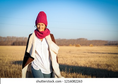 The concept of livestyle  outdoor in autumn. Close up of a young woman student in a warm autumn clothes, pink knitted hat looking funny, smilling, posing for the camera, walking on field, on  forest