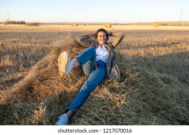 The concept of livestyle  outdoor in autumn. Close up of a young woman student in a warm autumn clothes looking funny, smilling, posing, lying on haystick around field