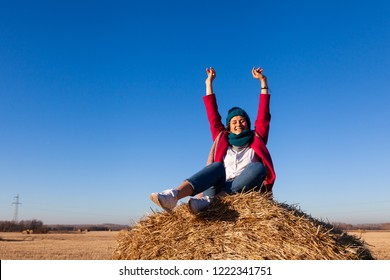 The concept of livestyle  outdoor in autumn. Close up of a young woman student in a warm autumn clothes looking funny, smilling, posing for the camera, sitting on haystick