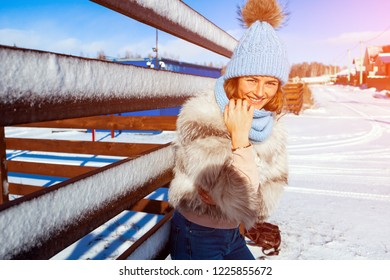 The concept of livestyle  outdoor in winter. A young woman student in a blue knitting hat,a white fur coat  smiles, looks into the camera and walks through the winter village, in the background fences
