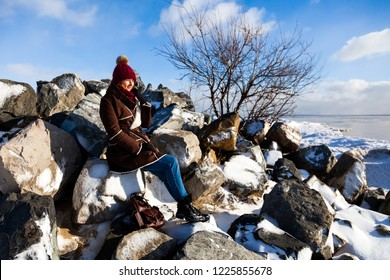 The concept of livestyle  outdoor in winter. A young woman student in a red knitting hat, a brown sheepskin coat sits on a stone rock covered with snow, enjoys winter and looks at the frozen sea
