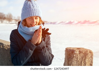 The concept of livestyle  outdoor in winter. A young woman student in a blue knitting hat and  coat  smiles, heats up and walks through the winter mountains