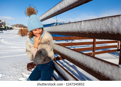 The concept of livestyle  outdoor in winter. A young woman student in a blue knitting hat and  furcoat  smiles, heats up and walks through the winter mountains