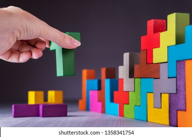 The concept of logical thinking. Geometric shapes on a gray background. Hand holding wooden puzzle element. Hand sets the element of the puzzle. Business building concept.