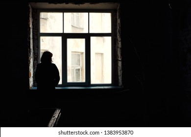 Concept of loneliness in the city, waiting and decision making. Woman looking out of the window in dark deserted house, Selective focus. Special light.